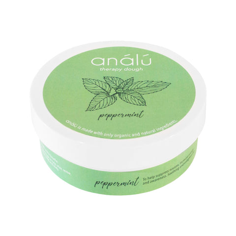 A small container with green packaging. There is white text on the lid that reads 'análú therapy dough. A small drawing of mint leaves is displayed underneath the text, indicating the scent. There is also text around the body of the container indicating its use.