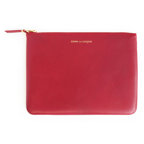 A flat red leather makeup pouch with a top zip and gold embossed letter along the top.