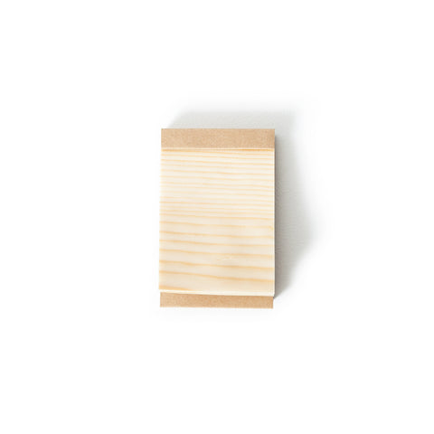 A  memo pad made of wood sheets. Sheets are affixed to cardboard cover.