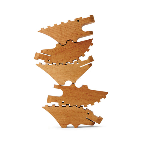 Facing sideways, a pile of natural wooden crocodiles are stacked up on top of each other interlocking to form a tower