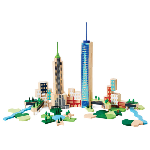 Against a white background is a photograph showing a frontal view of the building set. It is assembled to form a city scape including low buildings  of varying shapes and two skyscrapers. One skyscraper resembles Freedom Tower while the other is a simplified version of The Empire State Building. Integrated between buildings are several parks each featuring grassy areas, trees and water.
