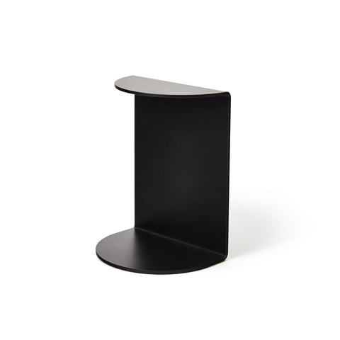 A photograph of a single black Reference Bookend standing up on its tall side, facing out at a forward angle.