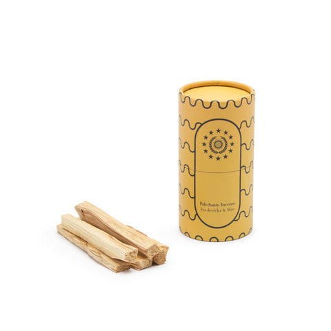 Image featuring a standing pale yellow colored cylinder with black linear wave details along its sides along with the company name and logo, as the container for a set of wooden incense sticks (Palo santo) laying down flat.