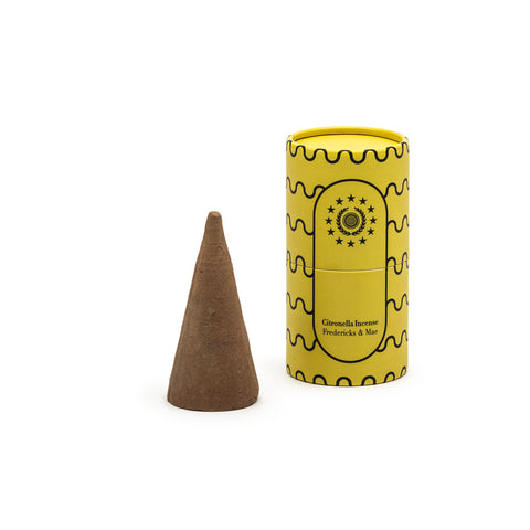 Image featuring a standing yellow colored cylinder with black linear wave details along its sides along with the company name and logo, as the container for a singular cone shaped incense.