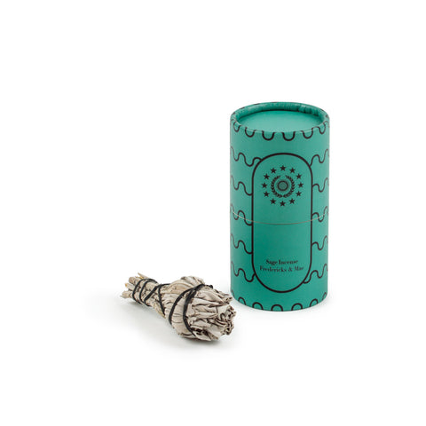 Image featuring a standing teal colored cylinder with black linear wave details along its sides along with the company name and logo, as the container for a set of small bunch of dried sage lying down down flat.