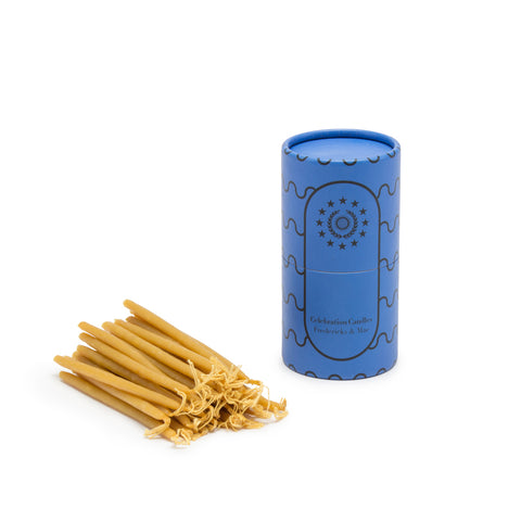 Image featuring a standing blue colored cylinder with black linear wave details along its sides along with the company name and logo, as the container for a set of small mustard yellow candle sticks laying down flat.