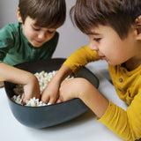 Two children reach into a black large square-shaped bowl filled with popcorn