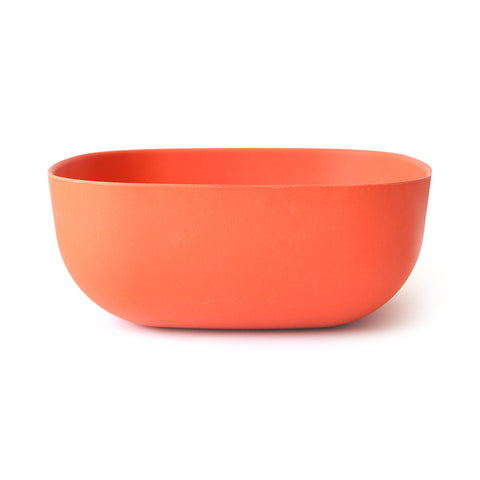 A large persimmon-colored serving bowl on a white background.