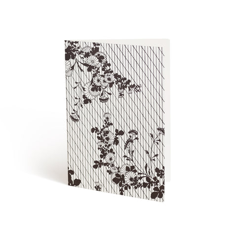 Printed in brown ink against a white background, the front of a card is covered in a lattice pattern. Layered over the lattice and bleeding off the edges, are two branches sprouting crysanthemum blossoms.