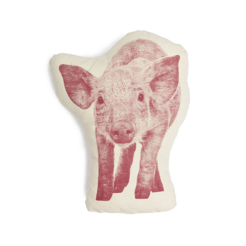 A photograph of a Fauna pillow in the rough shape of a pig. Centered inside a white outline, the pig, which is standing up and facing forward, is printed in gradations of pink.