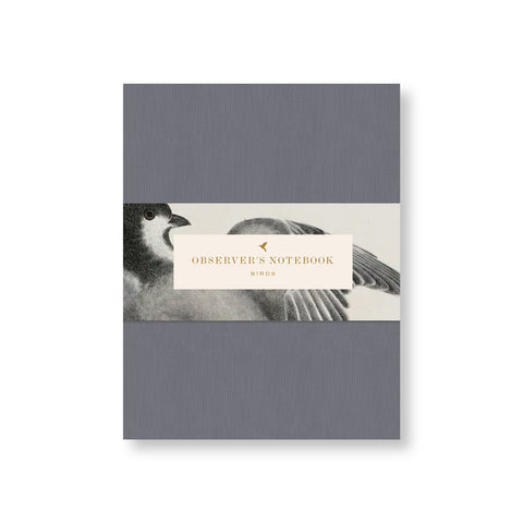 Gray blue canvas notebook cover with belly band with title in gold in vintage font surrounded by a watercolor illustration of a bird