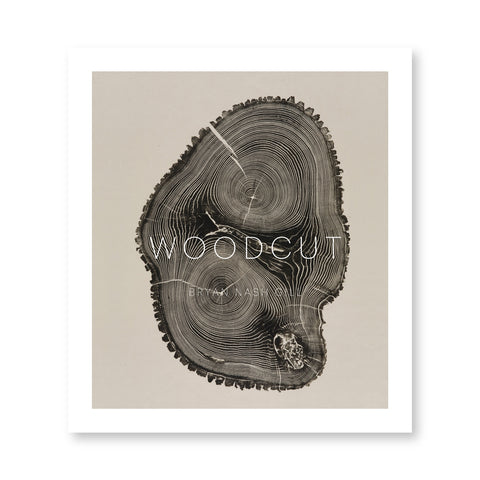 Beige book color with white boarder featuring a dramatic brown woodcut print showing two concentric ring sets in tree trunk