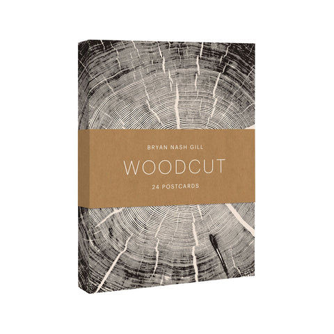 Postcard box with delicately rendered brown woodcut print with concentric tree rings partially covered by a brown belly band with title