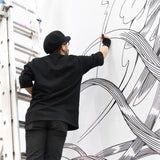 Artist on ladder drawing waves pattern on wall with Air Ink marker.