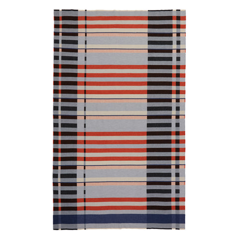 Full length Seal Stölzl Blanket on a white background, featuring a crisp graphic weave of strong black verticals and horizontal bands of navy, red, gray, peach and cream.