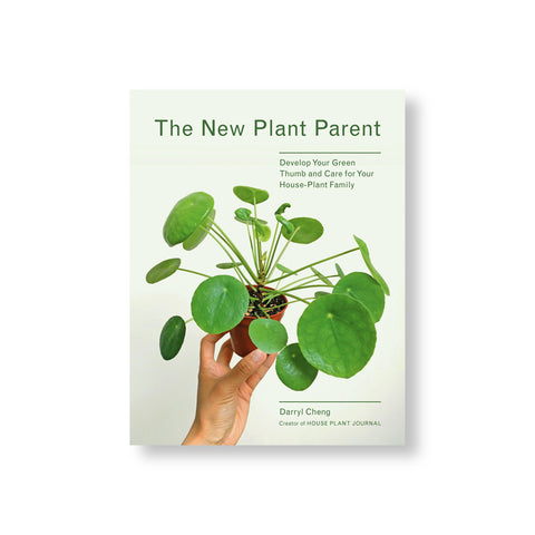 White book cover showing a hand holding a small potted plant with circular green leaves