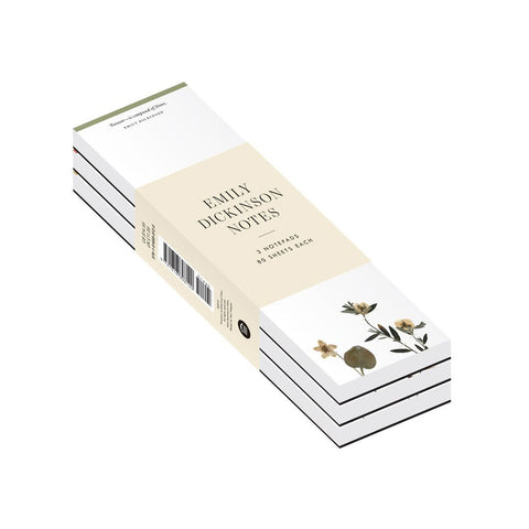 The slender notepads stacked with beige belly band with title information. Notepads are white with a quote at the top and images of pressed flowers at bottom