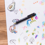 A CMYK Pen lays on a sheet of paper with colorful doodles created with cross hatching colors.