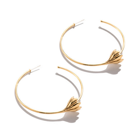 Brass hoop earrings that have a blooming flower at their bottom center.