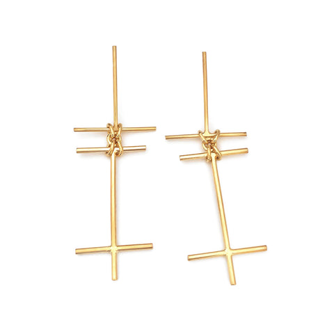 Two golden wire-like crosses linked with four small rings in the middle.