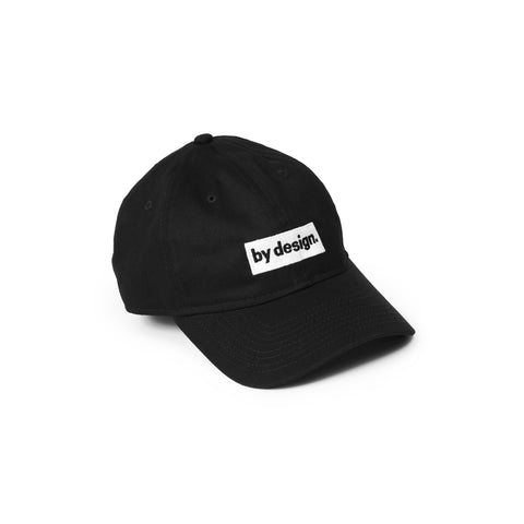 By Design Cap classic all-black minimalist baseball cap with a white rectangular patch above the visor with the words by design in black lower case letters followed by a period