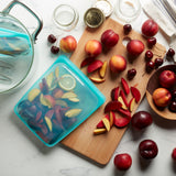 Kitchen counter with large aqua silicone pouch filled with and surrounded by cut fruits