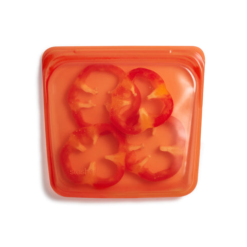 A transparent bright red colored silicone sandwich-sized resealable bag with red pepper slices.