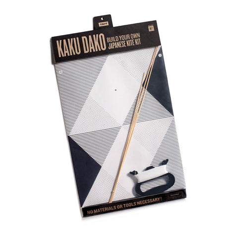 A Kaku Dako kite shown inside the transparent packaging. The kite's black and white geometric pattern is visible along with bamboo sticks and a kite handle with string.