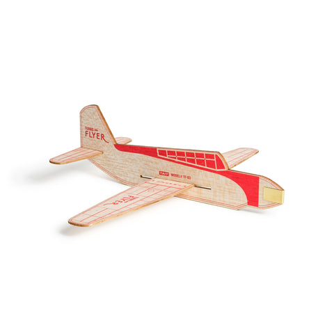 Sitting on a white surface, an image of an assembled turbo flyer airplane made of natural wood with red accents and logo on the tail.