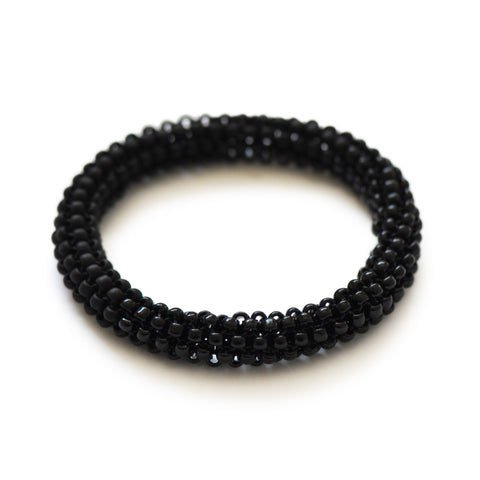 A flat, tubular bangle with a permanent knot. constructed as an uninterrupted length with no fastenings. Woven one bead at a time from super-strong nylon cord and Japanese glass seed beads. One half of the bangle is transparent, the other, frosted.