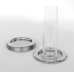 Stack of coasters next to one holding a clear glass, shot against white background.