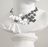 Mirror-polished u-shaped choker necklace with randomly placed rectangular shapes making up its structure, shot on a white statue.