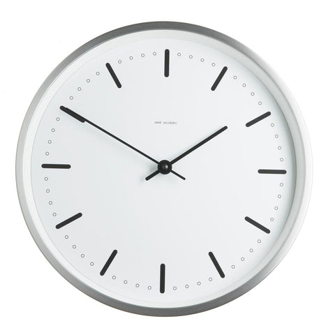 Circular white face clock with a minimalistic dial and two slim hands framed in a stainless steel case.