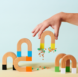 A photograph shows a group of magnets in different color variations; some stand upright, one on its side and one stacked on top of another. One magnet is being held up with a cluster of pins attaching to its magnetic ends.