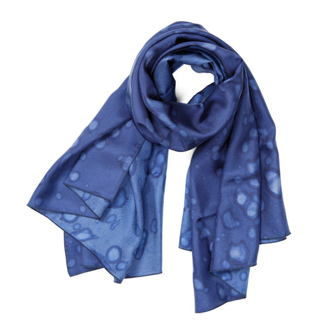 Made By Rain Scarf Large in Cobalt, looped at the top with the ends fanning out. The material is silky, and splattered with raindrops.