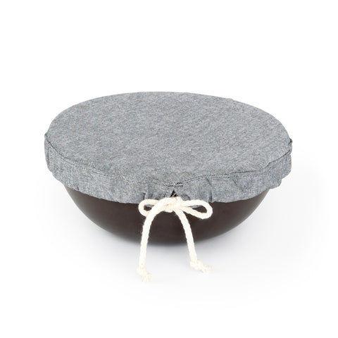 A round small sized grey cloth with tied draw string shown covering a small bowl.