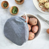 A grey cloth bowl cover is untied and hangs off the edge of a bowl exposing raw potatoes.
