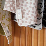 Close up detail of the color Bitmap pattern tea towels. Towels are loosely folded, showing that front and back patterns are reversed.