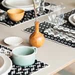 A cropped photograph of a tabletop scene. The table is set with placements, coasters and napkins showing how you can mix and match the black and white textiles. White dishes, glasses, a celadon mug and a natural wood vase accessorize the table.