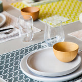 A cropped photograph of a tabletop scene. The table is set with placements, coasters and napkins showing how you can mix and match the color textiles. White dishes, glasses and natural wood bowls accessorize the table.