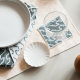 A detail of a tabletop scene. The table is set with placements, coasters and napkins showing how you can mix and match the beige and sage green textiles. A white plate, a glass, and a white scalloped dish accessorize the table.