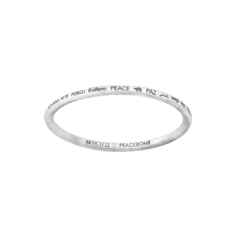 "Silver-colored bangle with the word ""PEACE"" engraved in different languages around the outside.  ""Article22 :: PEACE BOMB"" is engraved on the inner side of the bracelet."