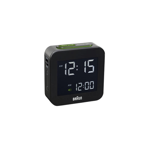 A square, compact travel or desk alarm clock in matte black with rounded corners and a shiny  square inset face with angular white digital numerals. Featuring the white Braun logo center bottom, a pop-up alarm button on top with a green rim and accents, and setting buttons on the left side.
