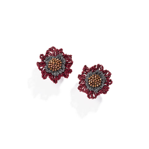 A pair of stud earrings with a double rose shape, with a cluster of faceted, copper-colored crystals at their center, surrounded by a dense circle of woven, metallic silver thread and an outer layer of red, woven, open-work petals in metallic thread.