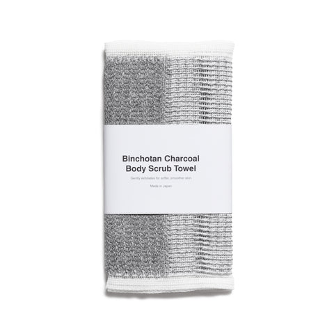 "A frontal image of a folded grey towel  with a rough texture and white border on the edges. A white wide paper band wraps horizontally around the towel and reads 'Binchotan Charcoal Body Scrub Towel"" in a simple black font."
