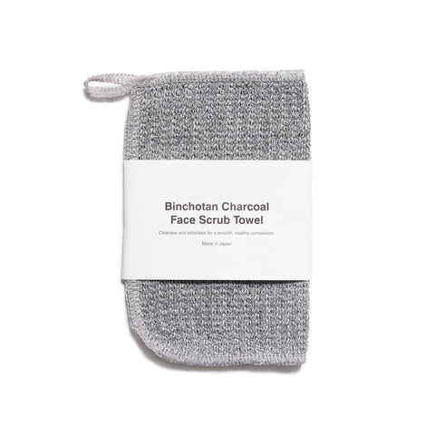 "A frontal image of a small grey textured towel with one rounded corner and a loop on the top corner for hanging. A white wide paper band wraps horizontally around the towel and reads 'Binchotan Charcoal Face Scrub Towel"" in a simple black font."