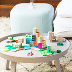 A photograph of a building block set featuring a colorful cityscape that is assembled on a small round wood table. The background is out of focus but appears to be a living room with a textured rug and upholstered furniture.