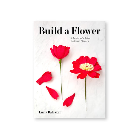 "Book cover featuring a full-bleed photograph of two vibrant red paper flowers on a marble background. Stencil-style text above reads: ""Build a Flower"""