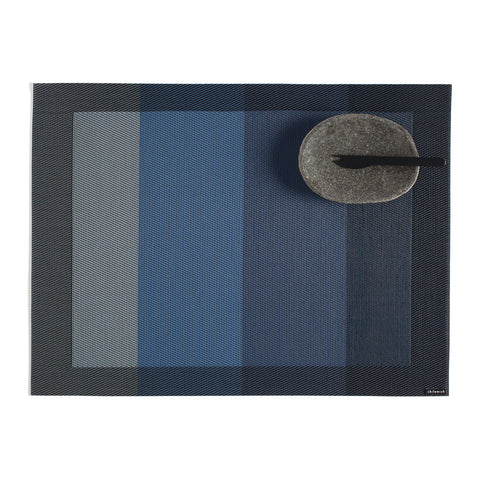 Rectangular woven mat with a black border, and inner pattern of four vertical blocks from gray to dark blue. Small oval granite bowl with black spork shown in upper right corner.