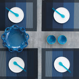 Overhead view of four gray to dark blue striped placements positioned at the corners of a grey surface, each with a white dessert plate and blue translucent dessert spoon, with a ceramic blue serving bowl and two small blue accent bowls in the middle.